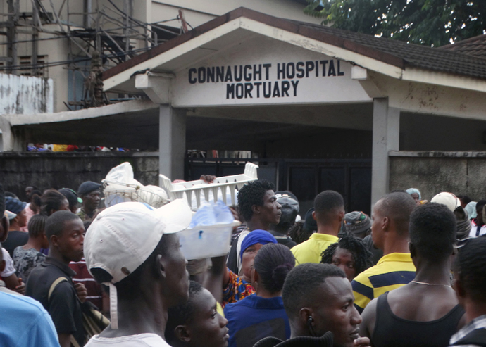 A crowd gathers at the main Freetown government Connaught Hospital Mortuary, where people wait for the chance to identify relatives. In the confusion and shock, not many had the opportunity to go in. More and more bodies were brought in as security forces tried to control the crowd and keep order. Photo by Phileas Jusu, UMNS.