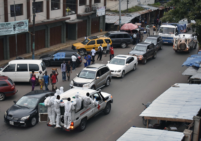 An ambulance with emergency personnel hanging on to the outside drives through a busy street in Freetown, Sierra Leone, after a mudslide devastated the Sugar Loaf Mountain Regent area. Photo by Phileas Jusu, UMNS.