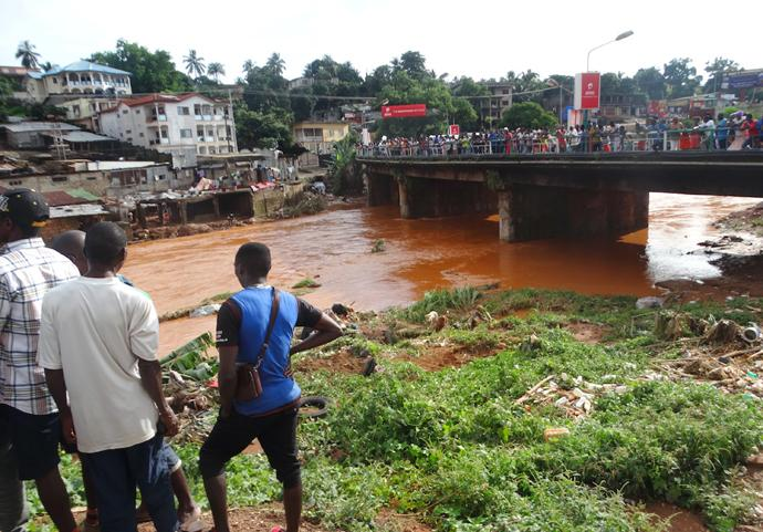 Volunteers wait at Wallace Johnson Bridge to spot and recover bodies in the aftermath of a mudslide and flooding at Sugar Loaf Mountain in Freetown, Sierra Leone. Photo by Phileas Jusu, UMNS.