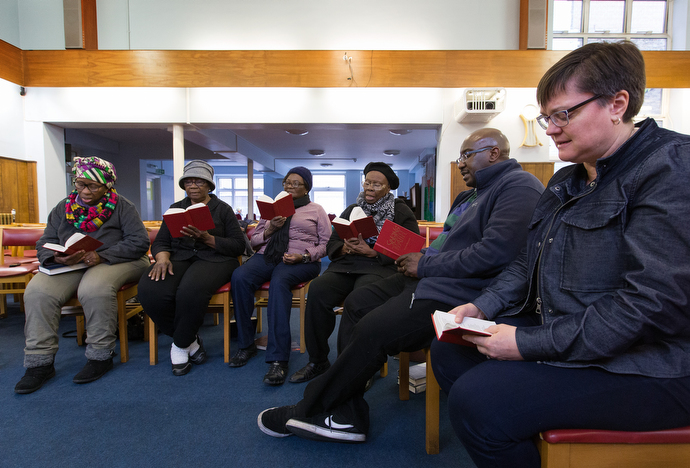 The Rev. Janet Corlett (right) takes part in a prayer and praise service at Bermondsey Central Hall Methodist Church. Photo by Mike DuBose, UMNS.
