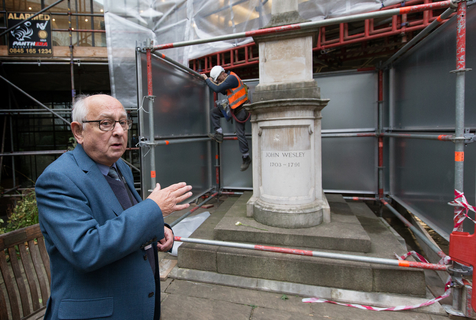 "Tour guide Allen Steel points out John Wesley's tomb in the garden at Wesley's Chapel while a worker climbs down from scaffolding erected to protect the historic site from encroaching construction in the area that has become known as the ""silicon roundabout"" because of the presence of high-tech industries. Photo by Mike DuBose, UMNS."