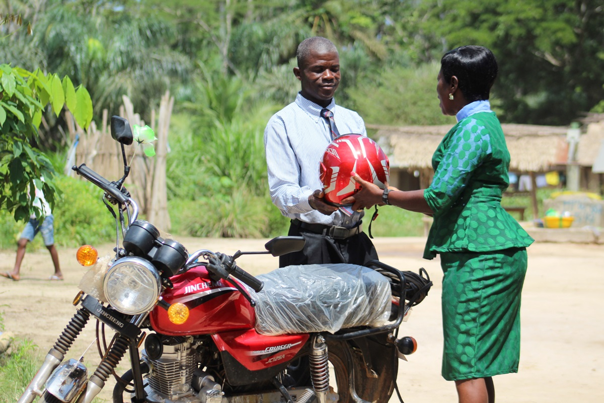 The Rev. Cecelia Marpleh, district superintendent for the Liberia Conference, presents a motorbike to Pastor William Kulah for his travels to Gbanjuloma United Methodist Church each week. With the motorbike, it takes him five hours to get to his assigned church. Photo be E Julu Swen, UMNS.