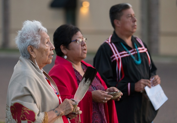 Native American scholar Henrietta Mann (left) and leaders of The United Methodist Church's Oklahoma Indian Missionary Conference, the Revs. Donna Pewo (center) and David Wilson, conduct a prayer ceremony for immigrant children held at the Casa Padre detention facility in Brownsville, Texas. The three prayed in a grassy median outside the facility, a former Walmart. It is the largest shelter in the U.S. for minors caught crossing the border illegally. Photo by Mike DuBose, UMNS.