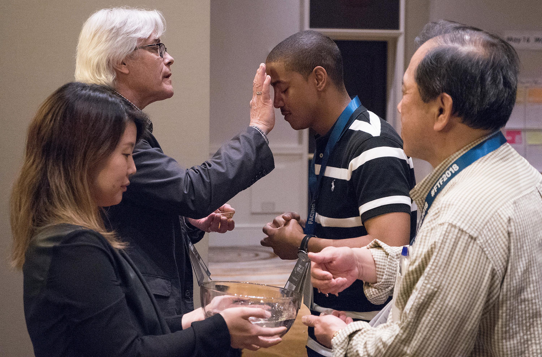 """Foto de archivo de Joey Butler, UMNS.  El Rev. Jerome R. DeVine (izquierda, atrás) hace la señal de la cruz sobre la Revda. Kyland Dobbins durante una reafirmación del bautismo en """"Facing the Future 2018"""", un evento para el clero en nombramientos trans-raciales e interculturales, llevado a cabo en la ciudad de Newark, estado de Nueva Jersey. DeVine describió el servicio como """"un recordatorio de cómo somos reclamados por la gracia de Dios en el bautismo, así como el don continuo de la gracia que nos sana y fortalece en medio de las tormentas de la vida y el ministerio""""."""