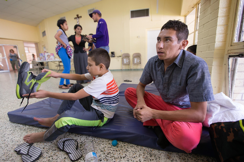 Oliver (derecha) y Anthony su hijo de 8 años descansan en un refugio desbordado de inmigrantes recientes, en la Basílica de Nuestra Señora de San Juan del Valle en McAllen, Tejas. Ellos huyeron de su Honduras natal por miedo a la violencia de las pandillas, y pidieron que sus nombres reales no se usen.
