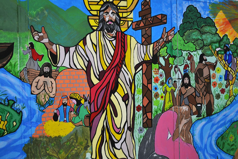 Al rededor de esta pintura mural que muestra la imagen de Jesús y diferentes episodios de las escrituras, se dieron cita líderes clérigos/as y laicos/as en Ciudad España, para coordinar acciones en favor de la población migrante hondureña.