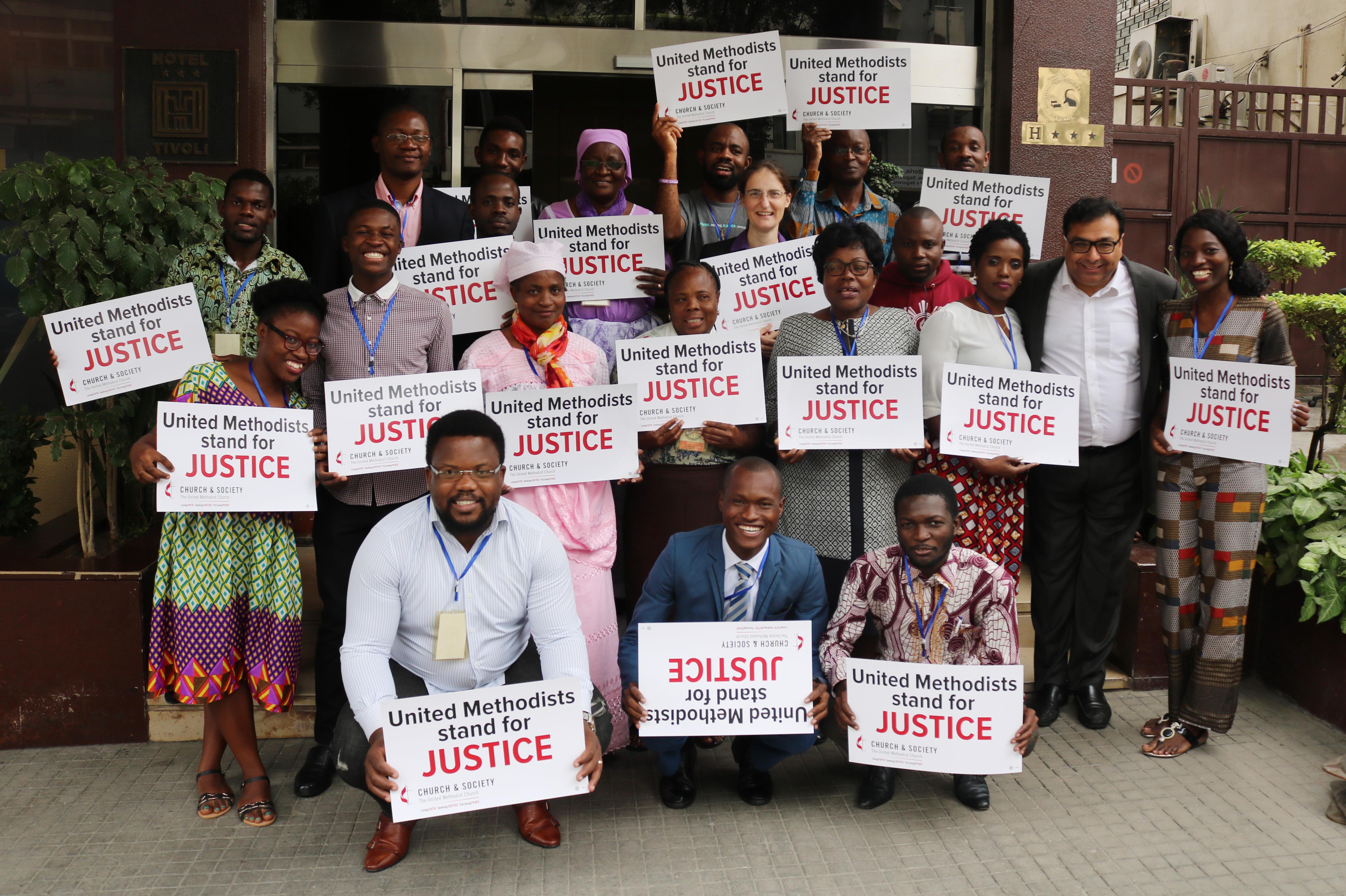 Metodistas Unidos seguram sinais após discussões em Luanda, Angola, sobre propostas da revisão dos Princípios Sociais da Igreja Metodista Unida. Foto por Orlando da Cruz, UMNS.