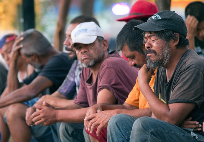 People living on the street, many of them migrants, pray during a worship service and dinner provided by El Divino Redentor Methodist Church at Mariachi Plaza in Mexicali, Mexico.