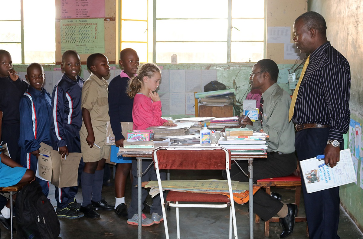 Mikayla Jaissle (center, wearing pink shirt) stands in line with other students while teacher Nicholas Chidzikwe checks her work at Hartzell Primary School in Mutare, Zimbabwe. The 10-year-old from Lakewood, Ohio, accompanied her mother, the Rev. Laura Jaissle, on the trip and attended class at the United Methodist school for two days. Photo by Eveline Chikwanah.
