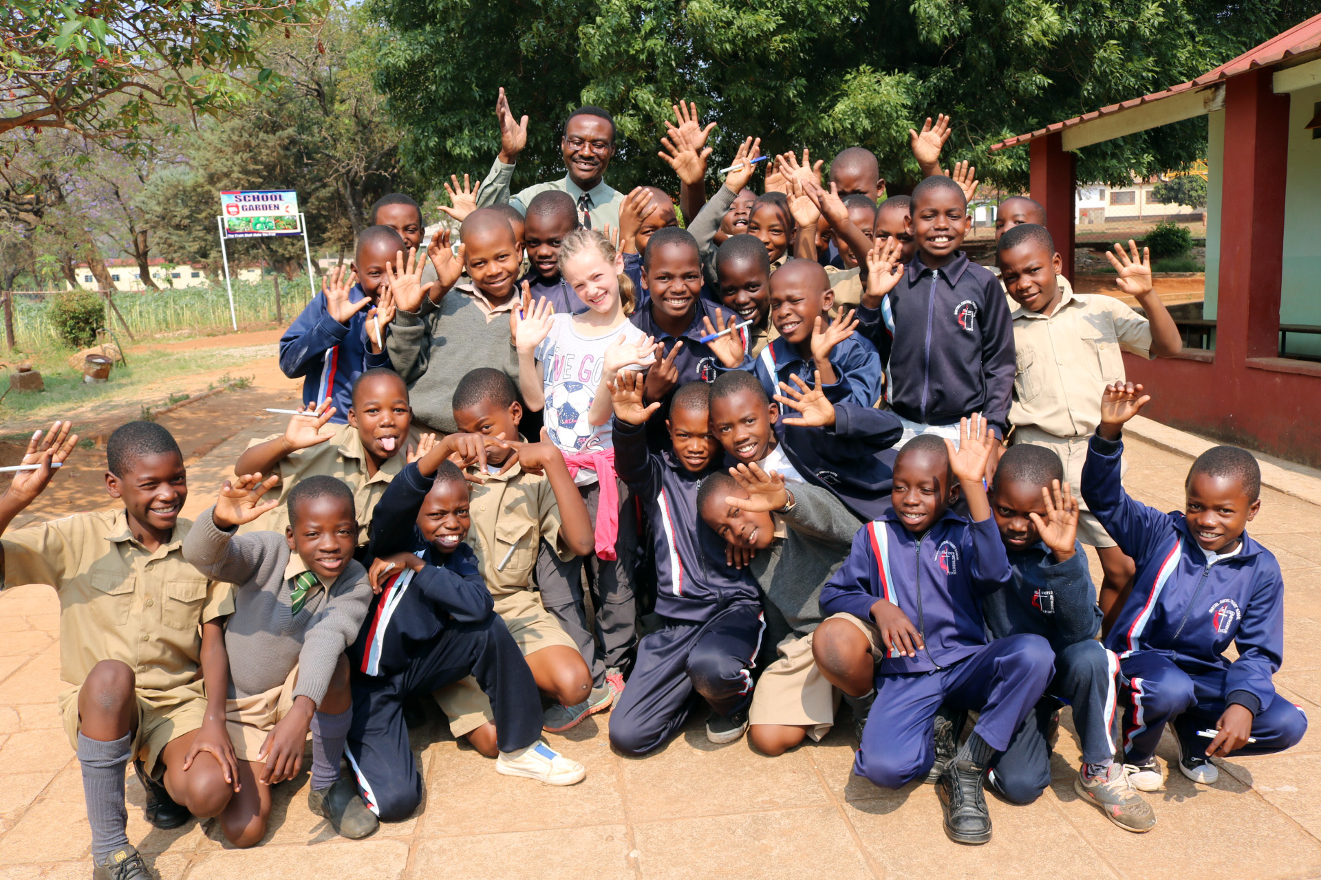 Mikayla Jaissle (center, wearing white soccer shirt) poses with teacher Nicholas Chidzikwe and classmates at Hartzell Primary School. Photo by Eveline Chikwanah.