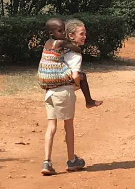 Mikayla Jaissle offers a piggyback ride to a classmate at Hartzell Primary School. Photo by the Rev. Laura Jaissle.
