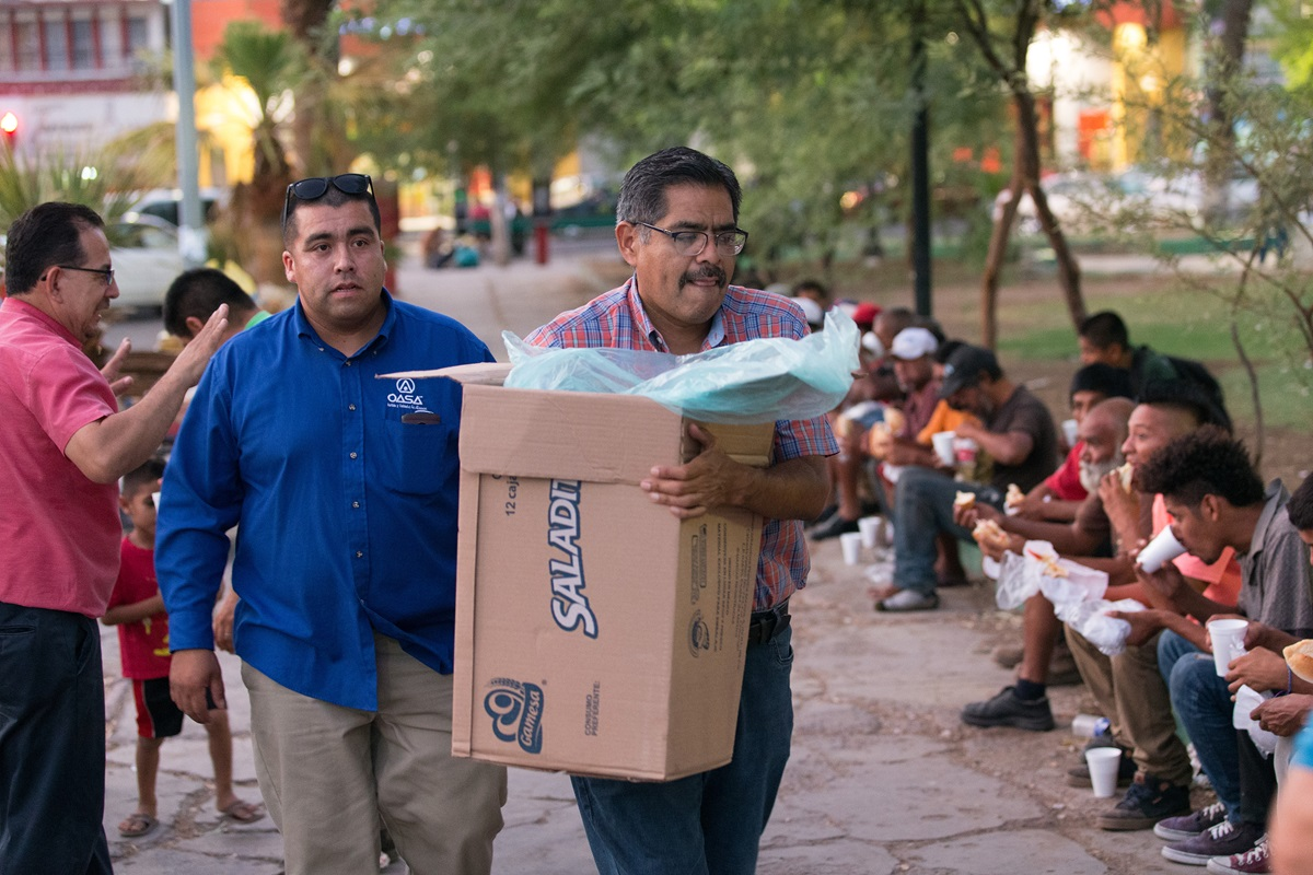 Bishop Felipe Ruiz Aguilar of the Methodist Church of Mexico (front) and Roberto Casares of El Divino Redentor Methodist Church help serve dinner to migrants and others living on the street at Mariachi Plaza in Mexicali, Mexico, in August 2018. Ruiz was among six bishops of the Methodist Church of Mexico who signed a statement urging better treatment of refugees. File photo by Mike DuBose, UMNS.