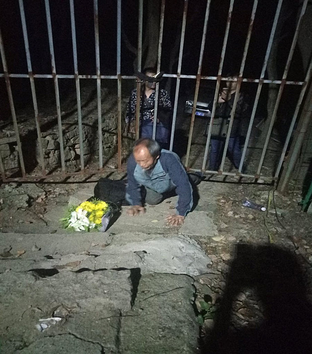Chinese activist Zhu Chengzi works his way under a fence at the Lingyanshan Cemetery in Nanjing, China, in this undated file photo. He intended to pay tribute to dissident Lin Zhao, who was executed in 1968. He was arrested by Chinese authorities and is still in custody as of October 2018.  Photo courtesy of Lian Xi.