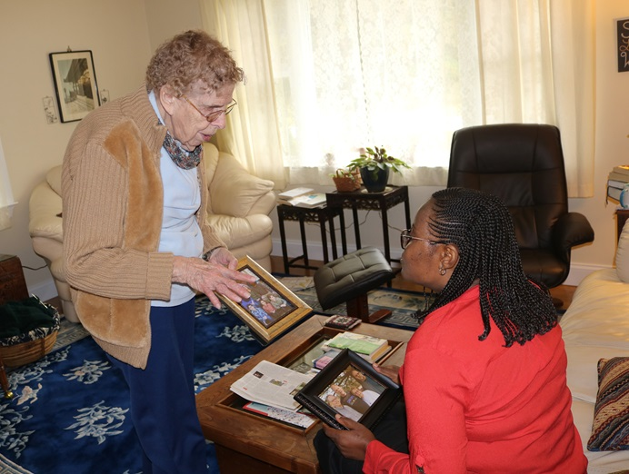 Dusty Knisley (left) of Calvary United Methodist Church in Dillsburg, Pa., shares her family story and photos with the Rev. Daisy Gbloh from Sierra Leone. Knisley hosted a team from the Sierra Leone Conference at her home. Photo by Phileas Jusu, UMNS.
