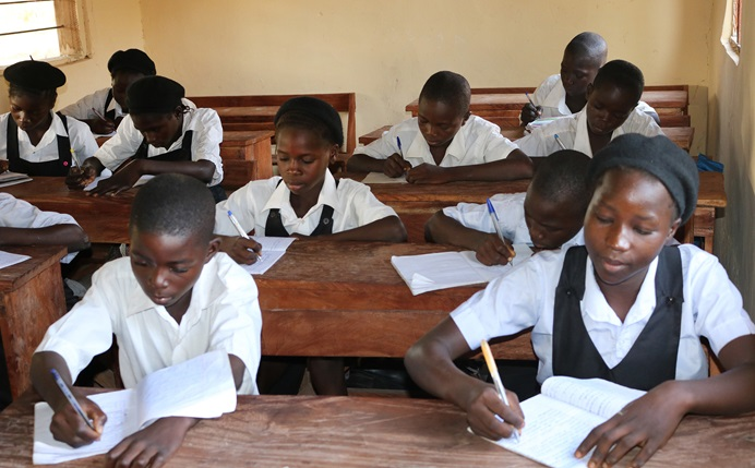 Students at the Guinter Memorial Secondary school write notes in their classroom. Photo by Richard Fidelis.
