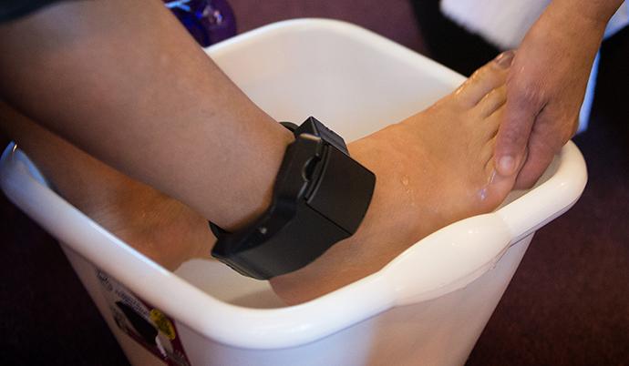 Una migrante de América Central, que lleva puesto un dispositivo de rastreo en su tobillo mientras persigue una solicitud de asilo en los EE. UU., participa en el lavamiento de pies durante la adoración en la Iglesia Metodista Unida de San Diego. Foto de Mike DuBose, Noticias MU.