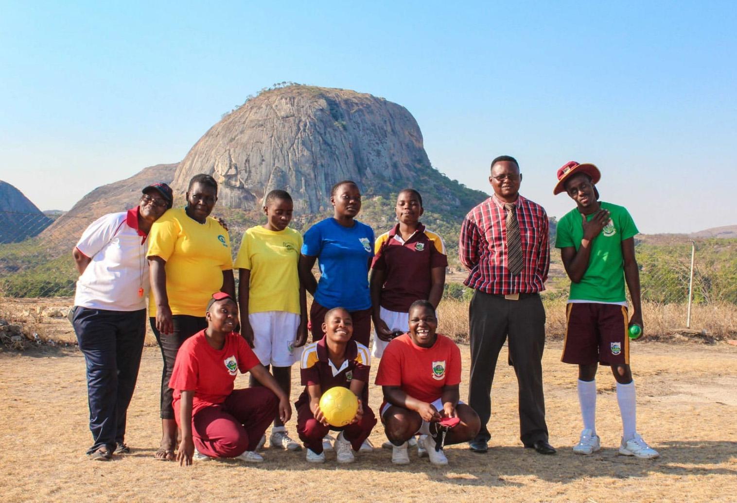 Seis estudantes da Escola Metodista Unida Murewa, no Zimbábue, foram selecionados para disputar a partida feminina da Associação Internacional de Futebol Cego no Japão, em 2019. Na primeira fila, da esquerda para direita, estão os alunos Fadzai Kimberley Nyakudya, Chengetai Chipanga e Monalisa Makoma; na fila de trás, da esquerda para direita, estão Teresa Mharadzirwa, a professora/guia Constance Tendere Munemo, Tanisha Zonde, a goleira Gellie Mawarire, Tarumbidzwa Taruvinga, o diretor esportivo Pilani Nyanhanda e Titus Tsiga. Foto de Chenayi Kumuterera, SMUN.