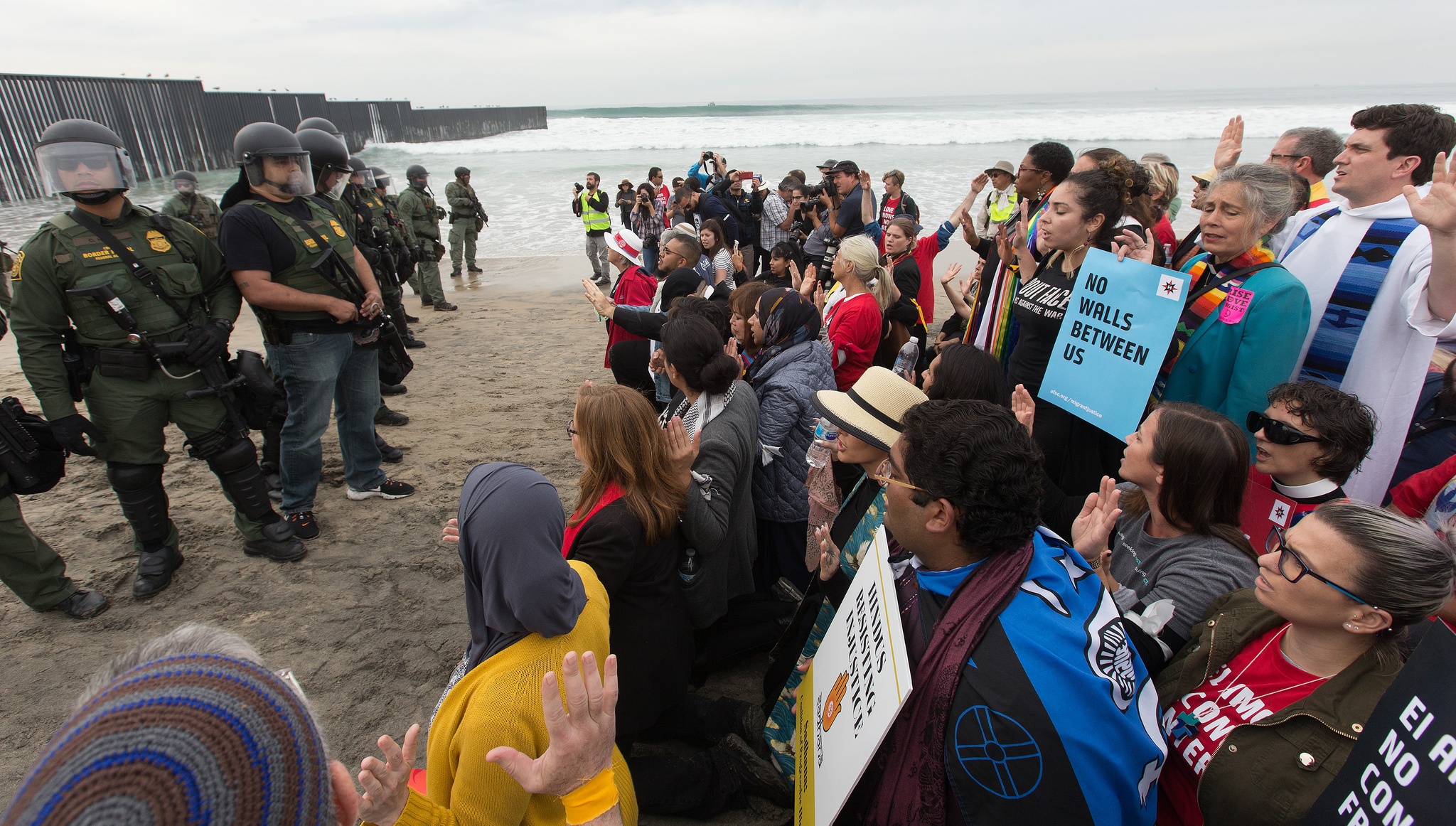 Faith leaders and other supporters of immigrant rights face U.S. Border Patrol agents at the fence between the U.S. and Mexico in San Diego. At bottom right is Emma Escobar of The United Methodist Church's Baltimore-Washington Conference. Photo by Mike DuBose, UMNS.