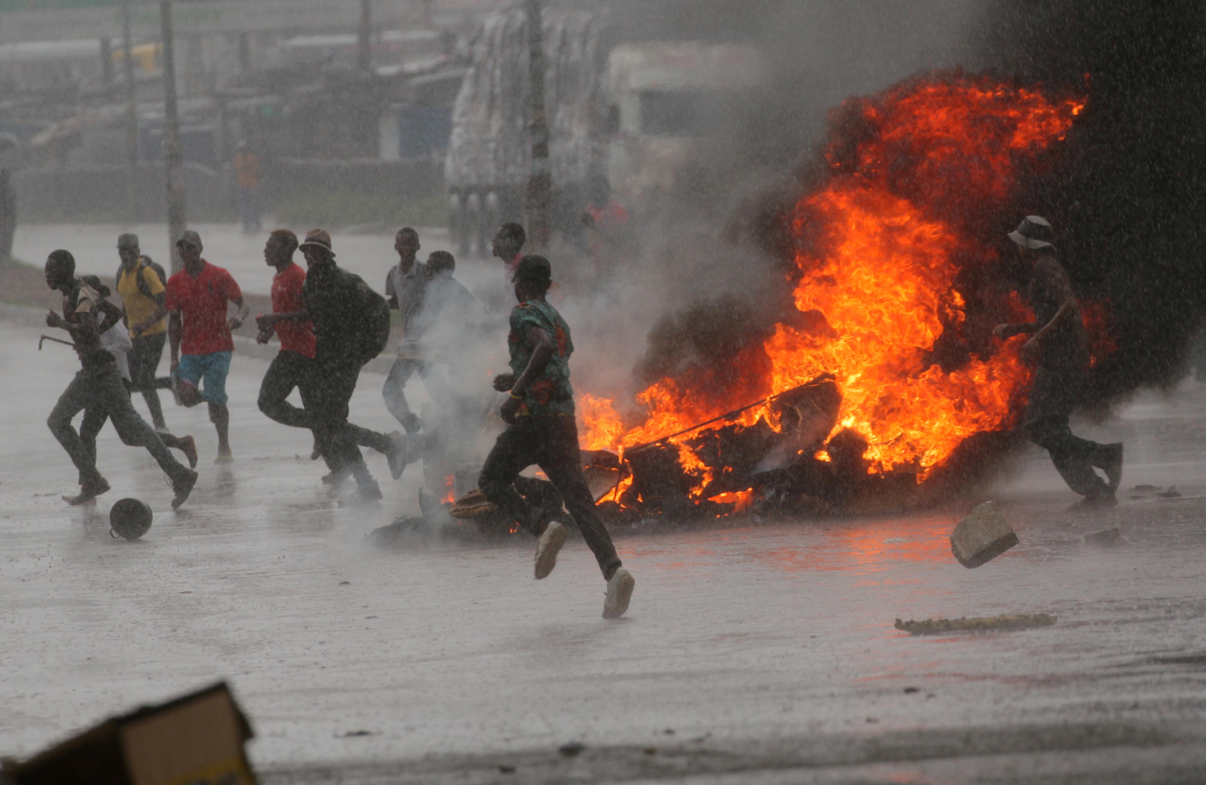 Pessoas correm em um protesto enquanto as barricadas queimam durante a chuva em Harare, Zimbábue. Metodistas Unidos estão pedindo por orações pela paz em meio a confrontos entre manifestantes e forças de segurança após um aumento nos preços dos combustíveis. Foto de Philimon Bulawayo, Reuters. Não reutilizar. Utilização única.