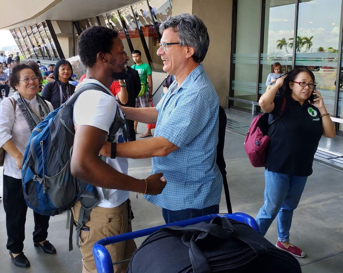 United Methodist missionary Tawanda Chandiwana (left foreground) is embraced by Thomas Kemper, head of the denomination's Board of Global Ministries, at the Ninoy Aquino International Airport in Manila, Philippines, after Chandiwana was released from a detention center and allowed to leave the country in July, 2018. The 13 agencies of The United Methodist Church are pursuing further accomplishments in 2019. File photo courtesy of Thomas Kemper, GBGM.