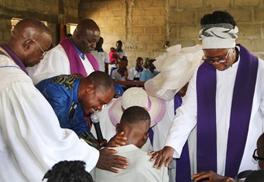 Visiting clergy from Freetown, Kenema and Kailahun, Sierra Leone, join the Rev. Judith Banya (standing right) to pray for Juana Jusu, who was partially paralyzed after an insect bite. Jusu traveled from Bomaru to join Baiwalla United Methodist Church  in celebrating its fifth anniversary. Photo by Phileas Jusu, UMNS.