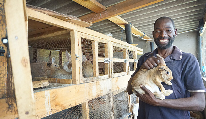 Damion Mutinhiri shows off one of the rabbits he and other members of the Deaf community have been raising in Mutare, Zimbabwe. The Ministry with Women, Youth and Children assisted the group with capital to start the rabbit-rearing project. Photo by Kudzai Chingwe.