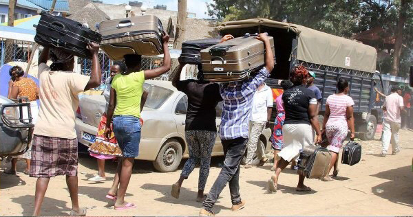 Families carry belongings after their apartments were demolished in Nairobi, Kenya. Photo by Gad Maiga.