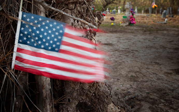 A U.S. flag flutters in the breeze outside the Eli Jackson Cemetery in San Juan, Texas. Descendants of the Jackson family are fighting to save the cemetery from being destroyed by a section of the proposed border wall along the Rio Grande. Photo by Mike DuBose, UMNS.