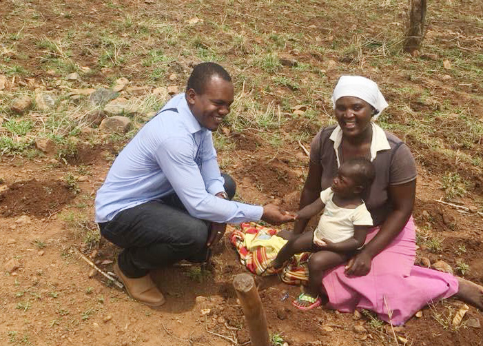 Cesar Lodiha Akoka, a theology student from Congo, helps a woman plant a seedling at Frickis Growth Point in Mutare, Zimbabwe. Akoka is one of several Africa University students working with local United Methodist congregations while studying abroad. Photo by Chenayi Kumuterera, UMNS.