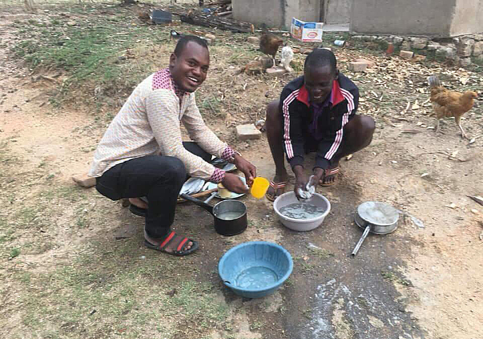 Cesar Lodiha Akoka washes dishes alongside a neighbor at Manica bridge shopping center in the Mutasa Nyanga community in Mutare, Zimbabwe. Akoka is one of several Africa University students working with local United Methodist congregations while studying abroad. Photo by Chenayi Kumuterera, UMNS.