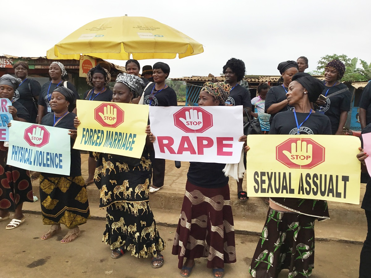 United Methodist Women in Liberia display signs to protest against the rising wave of violence against women and girls in Liberia. The peaceful demonstration took place during the group's 72nd annual session, held Jan. 21-27 in Marshall, Liberia. Photo by E Julu Swen, UMNS.