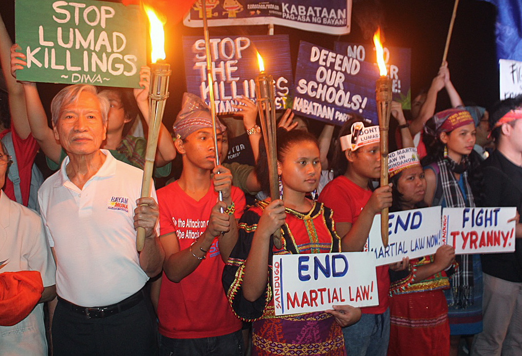 "Participants hold signs during an interfaith gathering at Rajah Sulayman plaza in Manila. Satur Ocampo (left), a well-known social activist, commended the interfaith initiative, calling it ""a signal that society should not remain silent in the face of such exigencies."" Photo by Gladys Mangiduyo, UMNS."