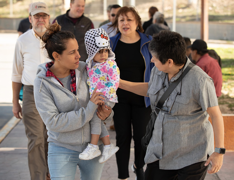 La Diácona metodista unida Cindy Johnson (derecha) camina para comprar medicamentos con Isabel, quien viajó con su hija desde Nicaragua hasta Matamoros, México, con la esperanza de solicitar asilo en los Estados Unidos. Kassandra, de 16 meses, sufría de fiebre y pérdida de peso mientras ella y su madre esperaban su turno para acercarse al puente que conduce a Brownsville, Tejas. Johnson, quien visita regularmente el campamento provisional, trajo a miembros del Grupo de Trabajo de Inmigración Metodista Unido para que conozcan de primera mano la situación de la inmigración. Foto por Mike DuBose, SMUN.