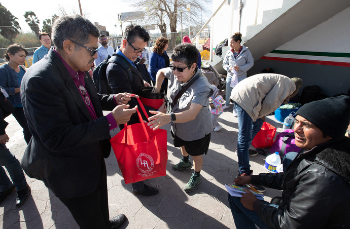 Bishop Felipe Ruiz Aguilar (left) of the Methodist Church of Mexico helps United Methodist Deaconess Cindy Johnson deliver food and sanitary supplies to migrants camped in Matamoros, Mexico, near the border with the U.S. Photo by Mike DuBose, UMNS.