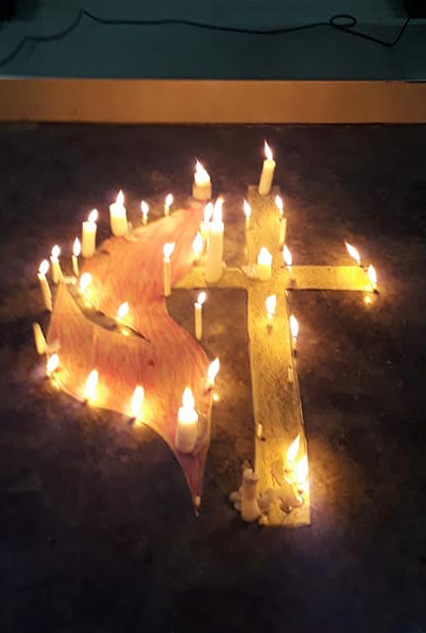 A cross and flame is surrounded by candles during a cluster prayer service at Dumoy United Methodist Church in Davao City, Philippines. Photo courtesy of Dania Soriano.