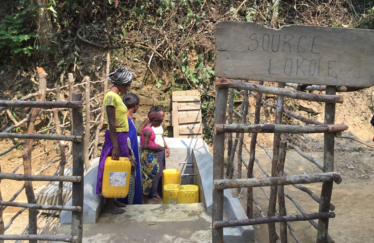 """Women fill plastic containers with water at """"Source Lokole,"""" a rehabilitated spring near the United Methodist Mission Lokole in Mikelenge, Congo. Photo by Judith Osongo Yanga, UMNS."""