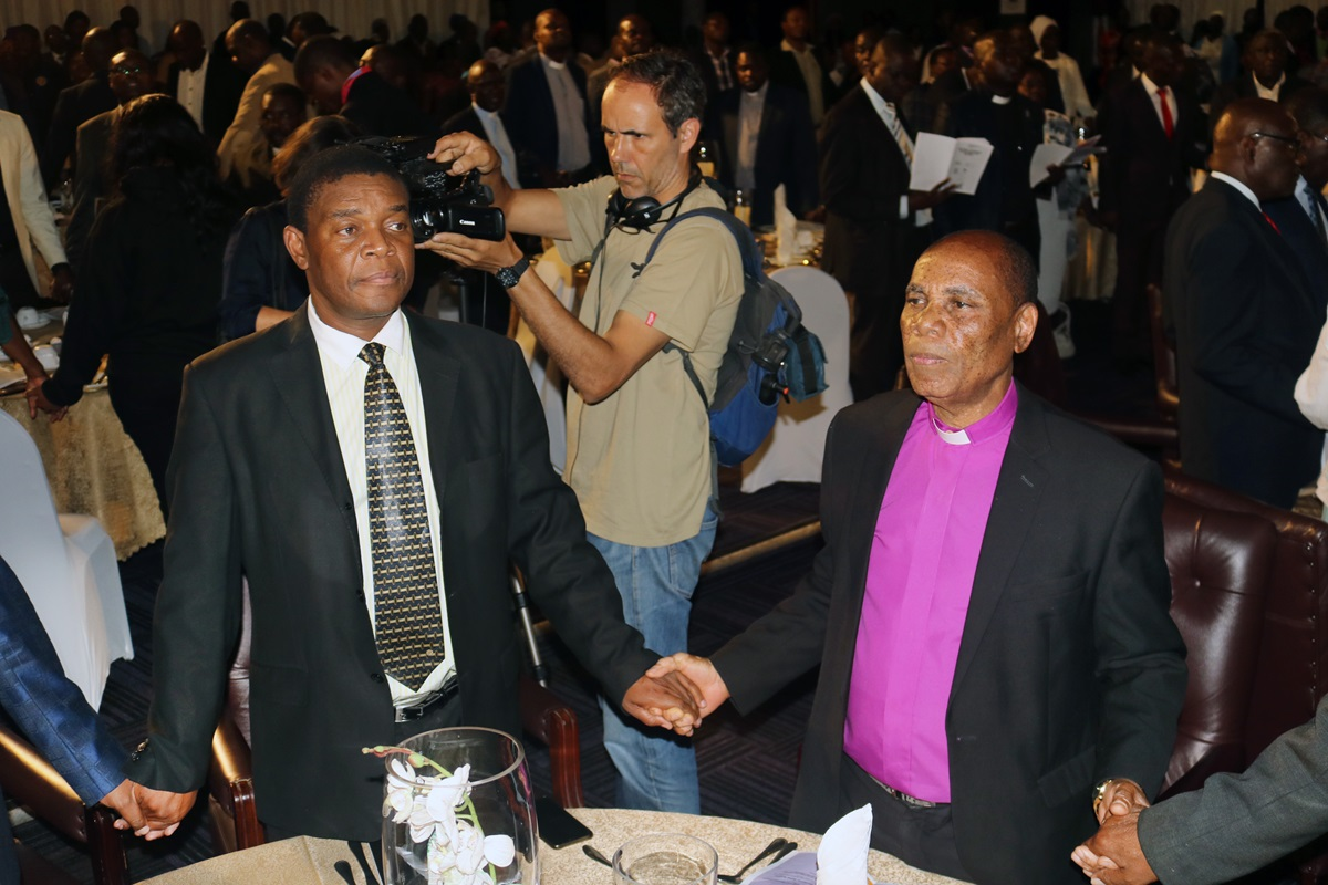 Zimbabwe Area Bishop Eben K. Nhiwatiwa, episcopal leader for the Zimbabwe East and Zimbabwe West conferences, joins hands with other Christians and political leaders at a national prayer breakfast and dialogue Feb. 7 in Harare, Zimbabwe. Photo by Tarui Emmanuel Maforo, UMNS.