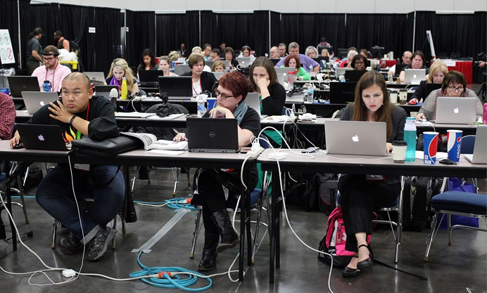 A General Conference newsroom is a busy place, hosting United Methodist News reporters, conference communicators, secular publication reporters and others. Kathy L. Gilbert (center) was among those filing stories from the newsroom at the 2016 General Conference in Portland, Oregon. Photo by Kathleen Barry, UMNS.
