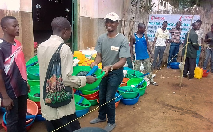 Jean Tshomba (center) hands food and other supplies to an internally displaced person from Bijombo, Congo, in front of New Jerusalem United Methodist Church in Uvira. Photo by Philippe Kituka Lolonga, UMNS.