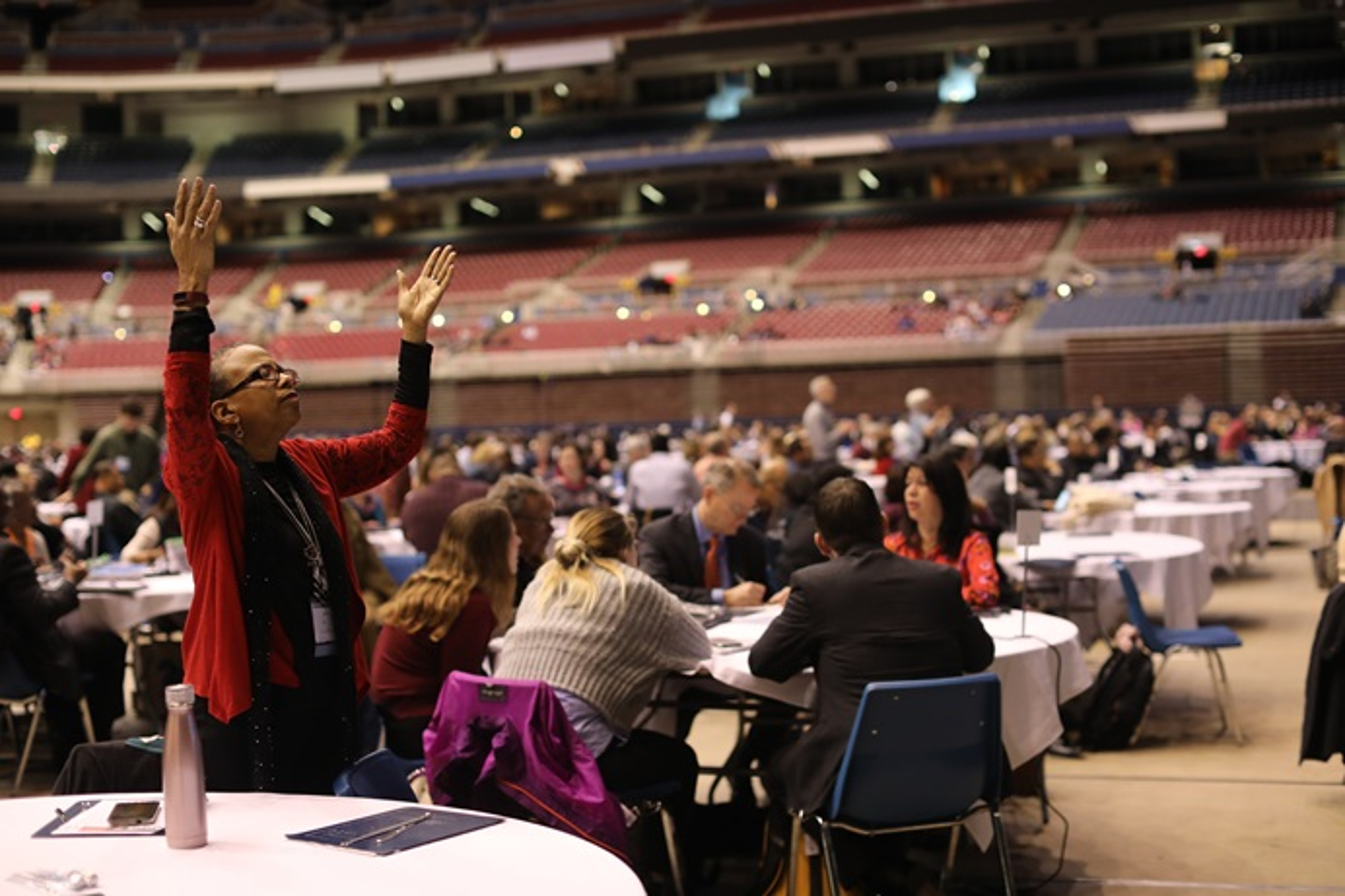 Cheryl Jefferson Bell (de pie), delegada de la Conferencia Anual Great Plains, levanta las manos durante la mañana de oración del 23 de febrero en la primera sesión de la Conferencia General Especial 2019 celebrada en la ciudad de San Luis. Foto por Kathleen Barry, SMUN.