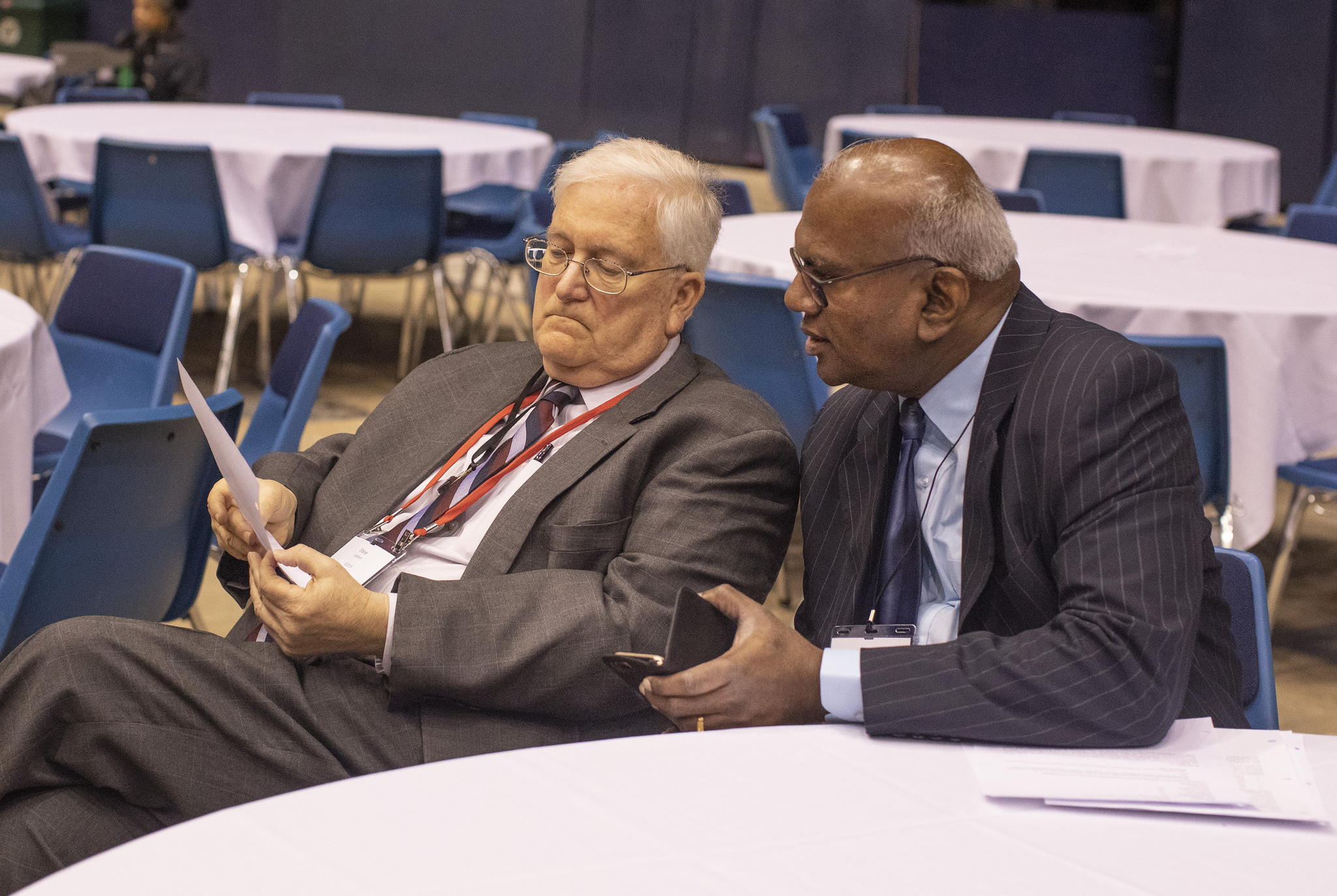 Steven Lambert (left), general counsel, and A. Moses   Kumar, general secretary and treasurer, both at The   General Council on Finance and Administration, listen   from the floor during the 2019 United Methodist General   Conference in St. Louis on Feb. 25. Photo by Kathleen   Barry, UMNS.