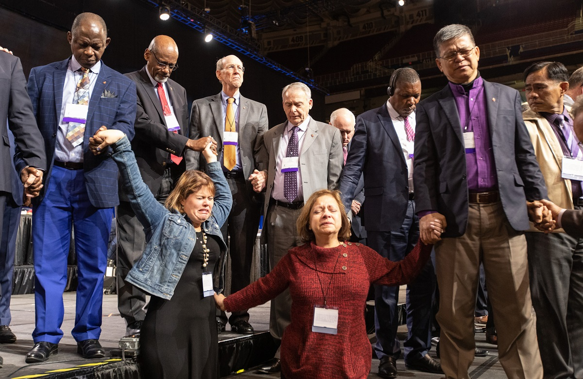 Florida delegates Rachael Sumner (front left) and the Rev. Jacqueline Leveron (front right) of the Florida Conference join in prayer with bishops and other delegates at the front of the stage before a key vote on church policies about homosexuality during the 2019 United Methodist General Conference in St. Louis. Photo by Mike DuBose, UMNS.