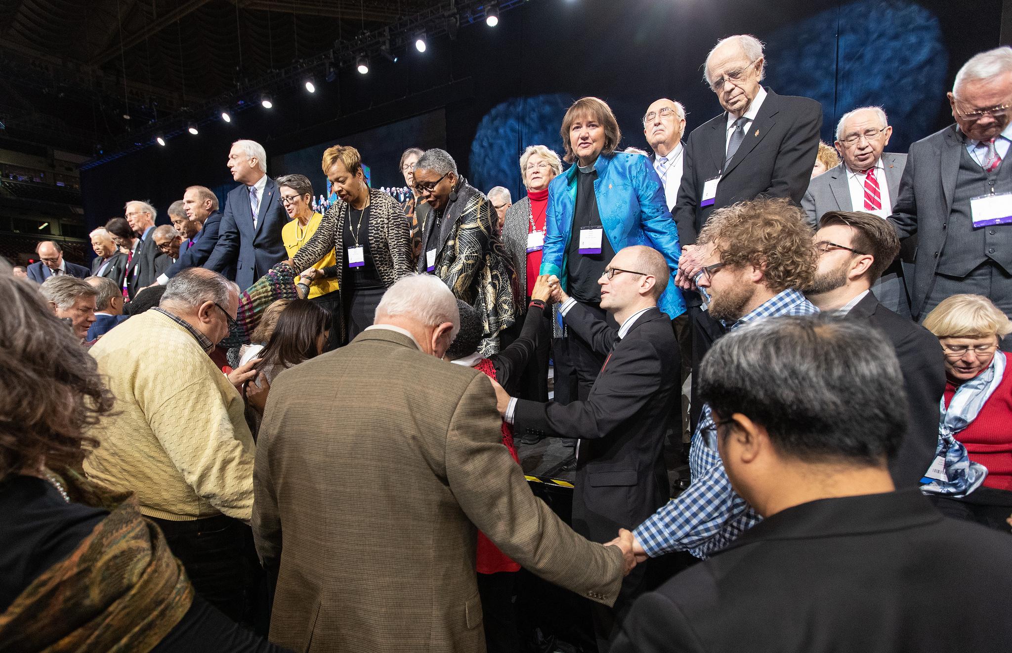 Image captions: 대의원들과 감독들이 세인트루이스에서 열린 2019년 연합감리교회 총회에서 동성애에 관한 교회 정책에 투표를 하기 전 무대 앞에서 기도하고 있다. 사진 Mike DuBose, UMNS.