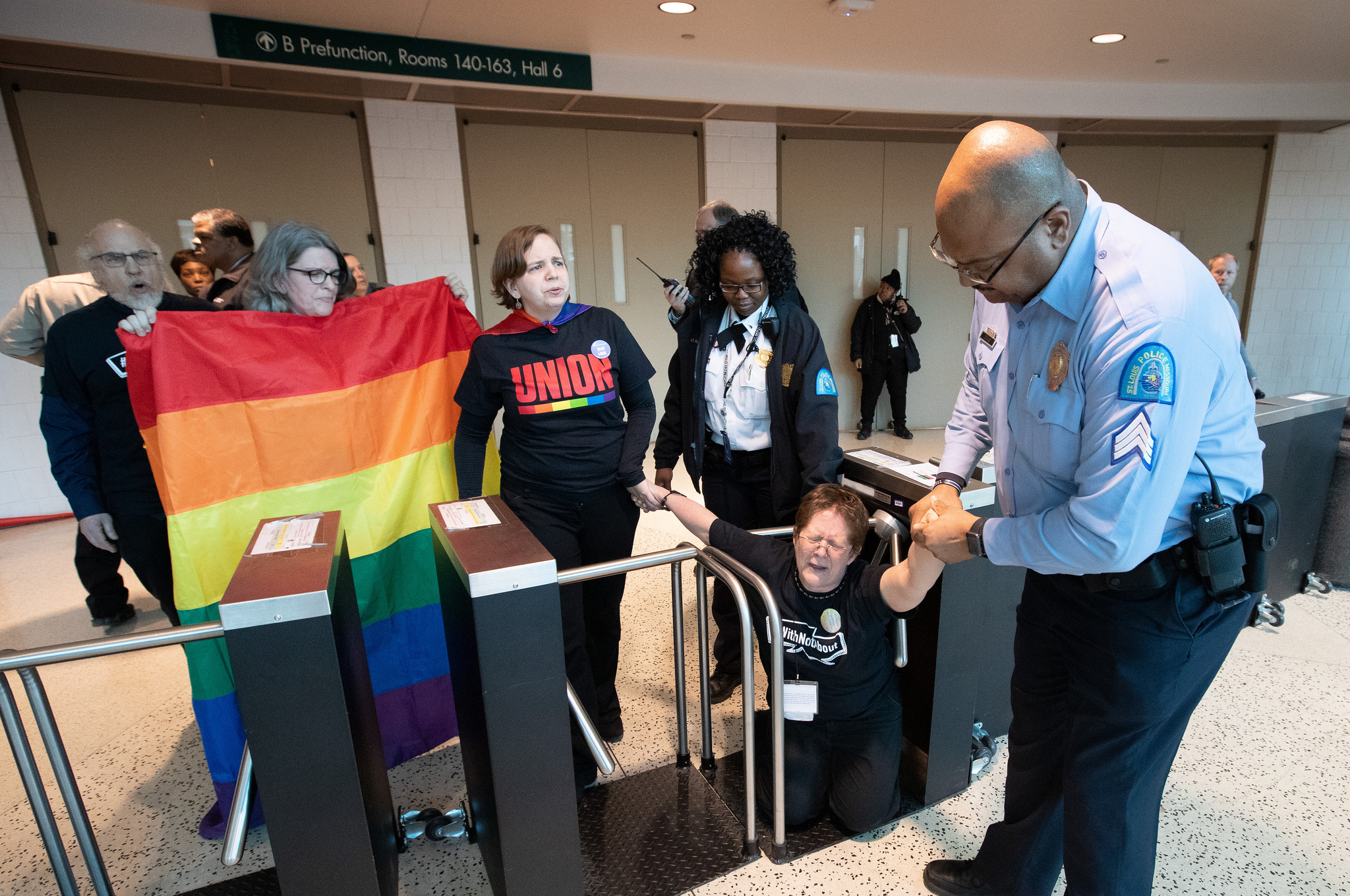 A St. Louis police officer pulls Carol Scott through a turnstile barricade in the Dome at America's Center in St. Louis, site of the 2019 United Methodist General Conference. Scott, a member of the Church of Saint Paul and Saint Andrew in New York, joined other supporters of full inclusion for LGBTQ persons in the life of The United Methodist Church in a protest outside the legislative assembly. Photo by Mike DuBose, UMNS.