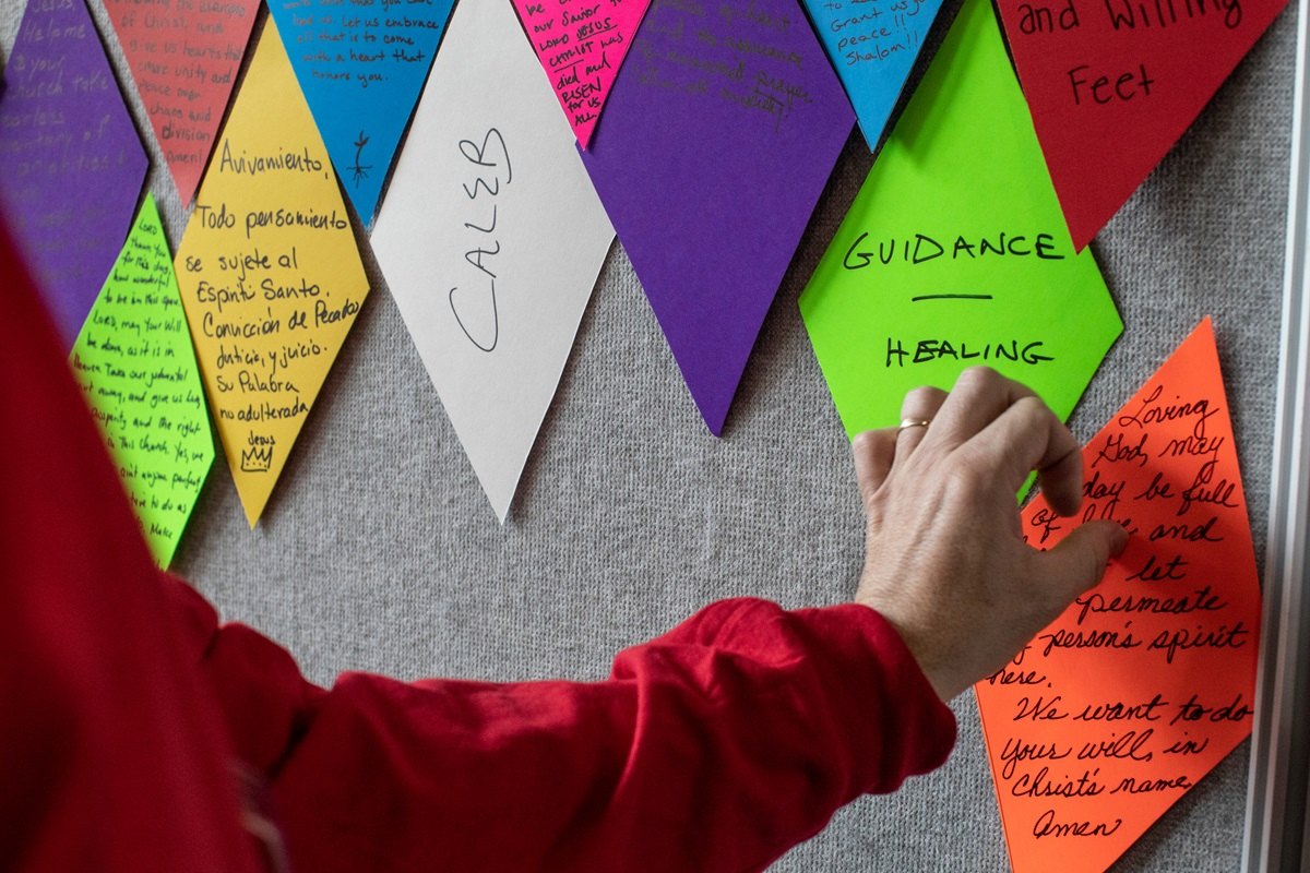 "Matt Henson, prayer room volunteer, creates a ""stained-glass"" wall out of prayers offered by attendees of the 2019 General Conference in St. Louis. Photo by Kathleen Barry, UMNS."