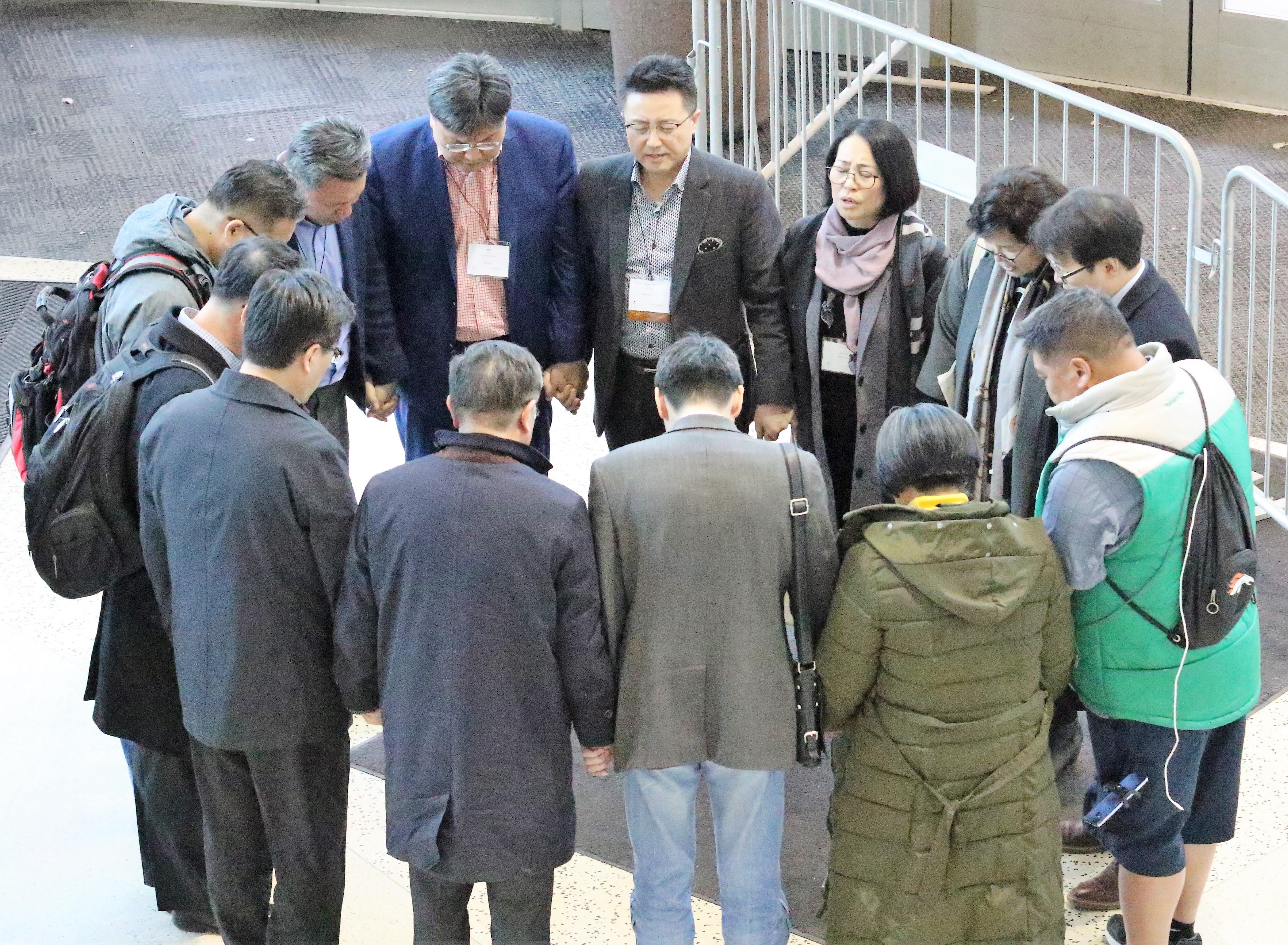 총회 기간에 한인연합감리교인들이 총회장 입구에서 기도하고 있다. 사진 김응선 목사, UMNS