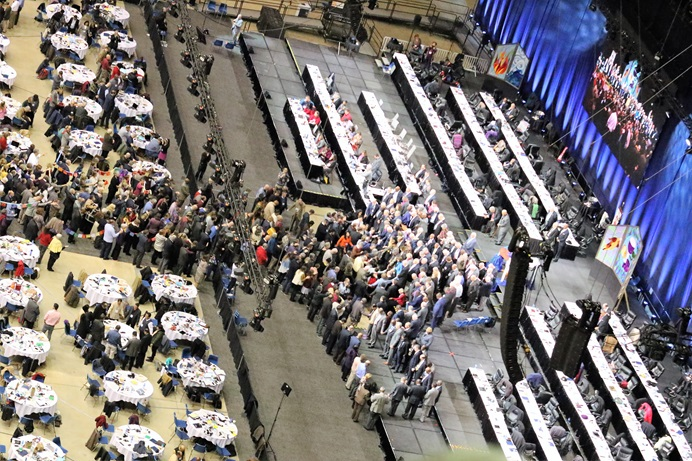 Delegates and bishops join in prayer at the front of the stage before a key vote on church policies about homosexuality during the 2019 United Methodist General Conference in St. Louis. Photo by the Rev. Thomas Kim, UMNS.