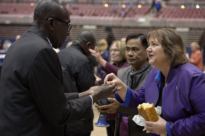 Bishop Karen Oliveto (right) shares bread with a delegate during a February 23, 2019, worship service in the special session of the General Conference of The United Methodist Church. Oliveto leads the Mountain Sky Area of The United Methodist Church.  Photo by Paul Jeffrey, UMNS.