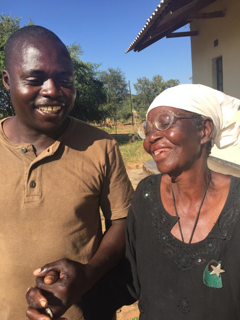 Artwell Chidhakwa, a driver at United Methodist Nyadire Mission Hospital, holds hands with Maduni Jangamu at an eyeglasses clinic in Dindi, Zimbabwe. Photo by Chenayi Kumuterera, UMNS.