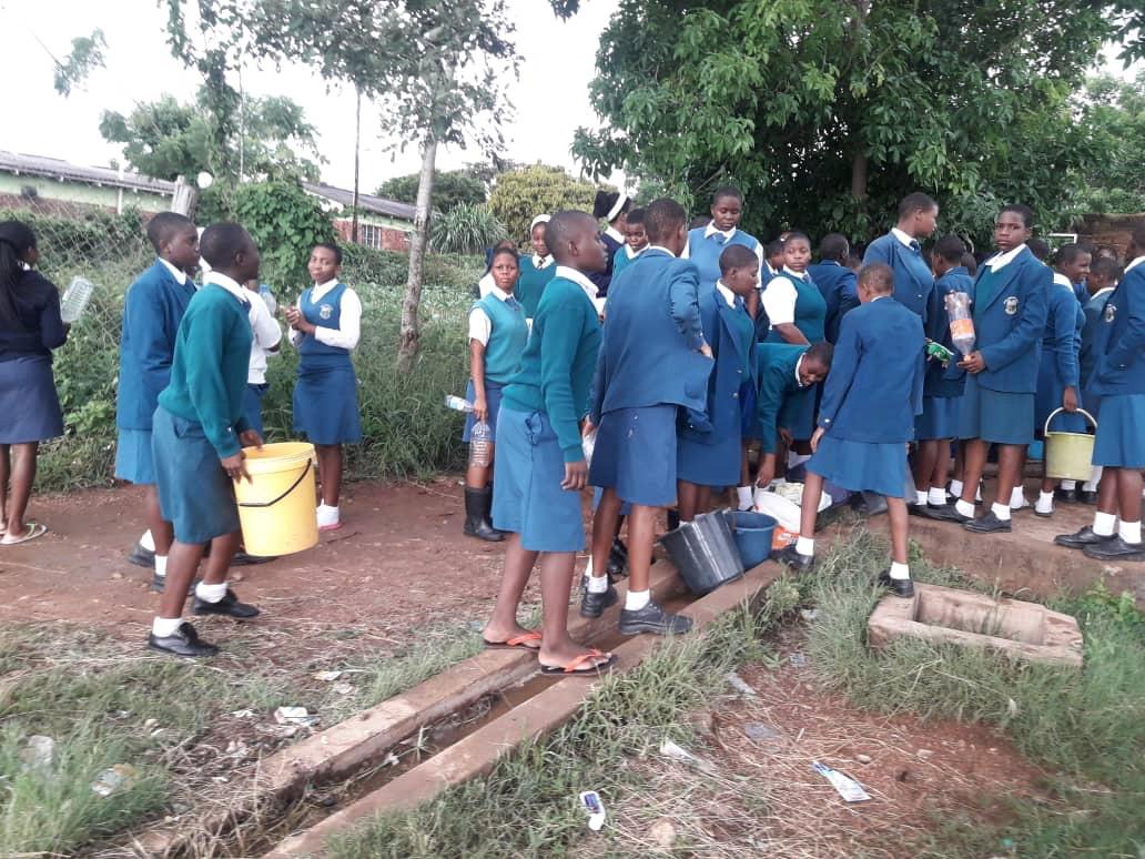 Lydia Chimonyo Estudantes da High School de meninas carregam baldes para coletar água em um poço em Chimanimani, Zimbábue. Não há água corrente na escola desde que o Ciclone Idai danificou a estação de tratamento da água da escola. Foto do Rev. Duncan Charwadza.